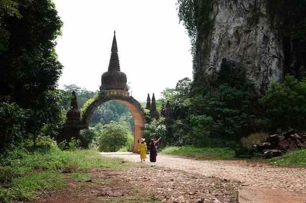 태국 수랏타니 주(surat thani province)의 카오나이루앙 다르마 공원(khao na nai luang dharma park) 또는 푸타와디(phutthawadee) 아치의 전경에 주황색 꽃과 푸른 잔디가 있습니다.