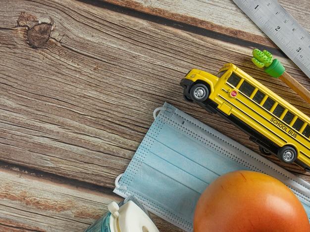 教育または医療の概念のためのスクールバスと木製のテーブルのマスク