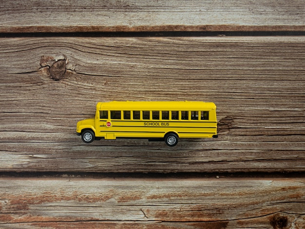 Школьный автобус на деревянном столе для образования или обратно в школу концепции
