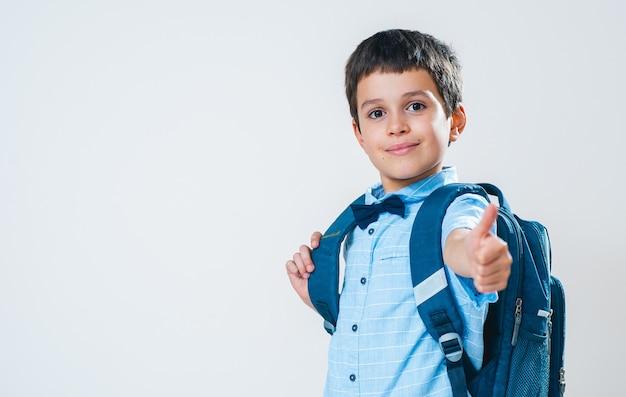 Школьник в рубашке с бабочкой и рюкзаком за спиной показывает большой палец
