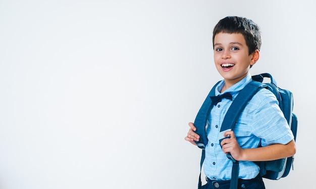 Школьник в рубашке с бабочкой и рюкзаком за спиной стоит полоборота и смеется