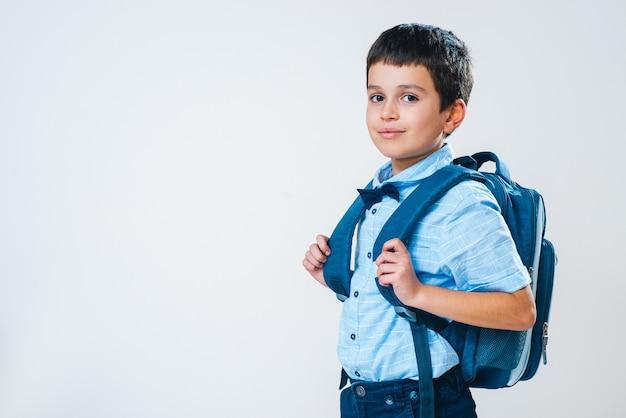 Школьник в рубашке с бабочкой и рюкзаке стоит в полоборота за спиной и улыбается