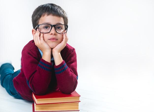 Школьник в свитере и очках лежит, положив руки на стопку книг, и смотрит на нас.