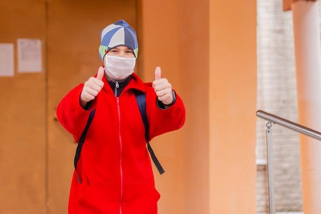 Школьник показывает класс в защитной маске