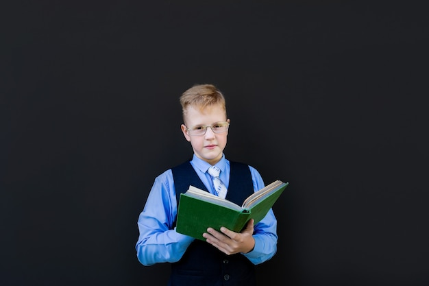 Школьник с книгой на черном фоне