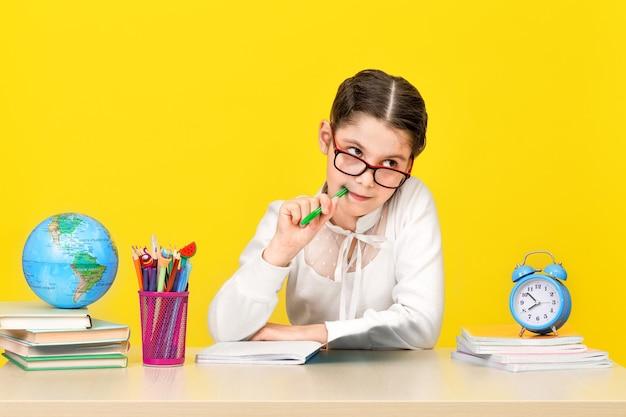 女子高生は机に座って、黄色の背景でタスクの決定について考えます。学校に戻る。新しい学年。子供の教育の概念。