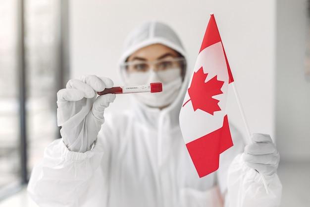 コロナウイルスのサンプルとカナダの旗を持つつなぎ服の科学者