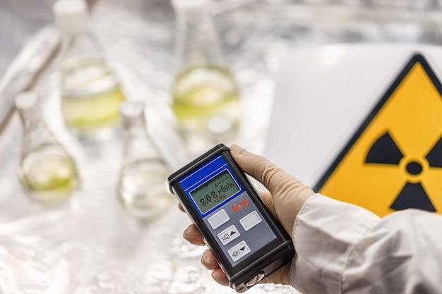 Ученый измеряет уровень радиации по признаку радиационной опасности с помощью дозиметра