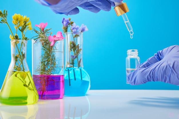 科学者の手は、化粧品のボトル、植物を背景にした試験管を持っています。