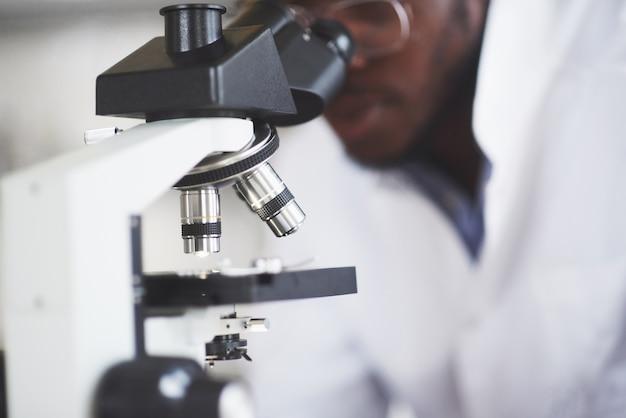Ученый работает с микроскопом в лаборатории, проводя эксперименты и формулы.