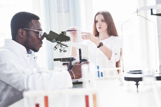 Ученый работает с микроскопом в лаборатории, проводит эксперименты и формулы.