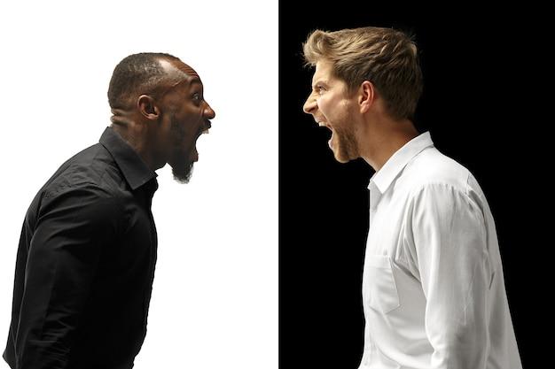 悲鳴を上げるアフロと白人の男性。混血のカップル。白と黒のスタジオで男性モデルのダイナミックな画像。人間の顔の感情の概念。