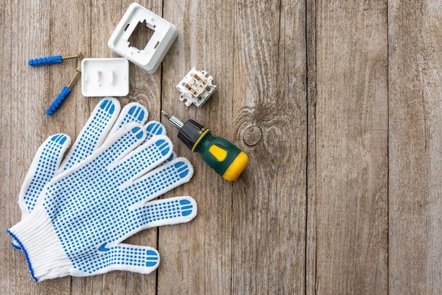 ネジとスイッチは手袋と一緒に木製のテーブルにあり、フラットレイ