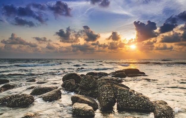 夕焼けの低い照明の海と岩。