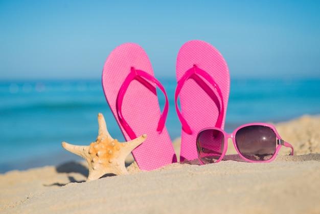 海、ビーチ、砂、女性用アクセサリー:ピンクのビーチサンダル、サングラス、ヒトデ