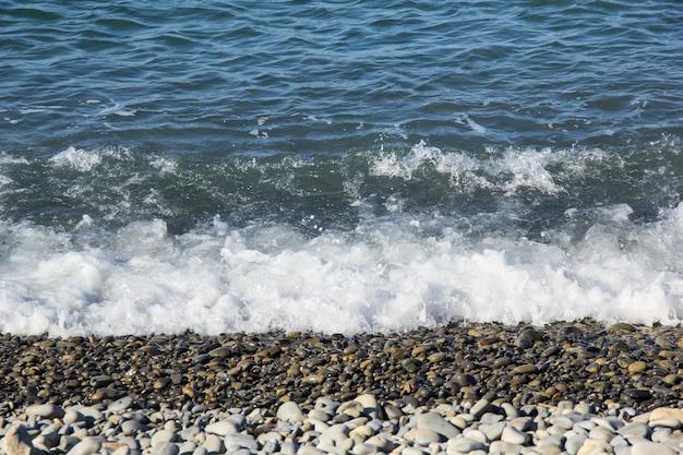 夏の空の小石のビーチの海の泡の波