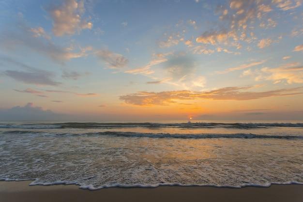 夕焼けの砂浜に海が打ち寄せています。海の景色を背景に青オレンジ色の空。