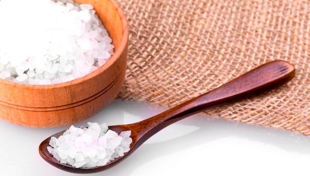 Морская соль на чашке с ложкой и мешковиной
