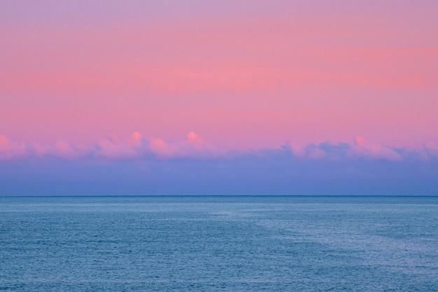 구름 아래 바다. 환상적인 북극 보라색 저녁 최소한의 바다 경치. 소프트 포커스.
