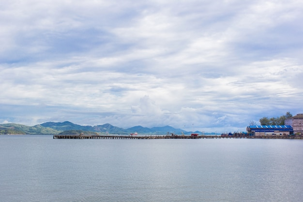 海の景色と空のある港は雲だらけです。背景に山があります。