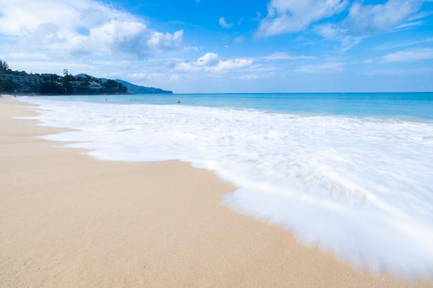 海の波がビーチで白い泡をスプレーします。