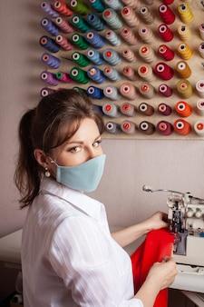 Швея в маске перекрывает край ткани будущего красного платья.