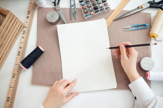 재봉사는 재봉을 위해 미래의 드레스를 스케치합니다.