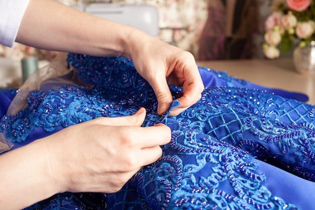 仕立て屋はドレスにレースとビーズを縫います