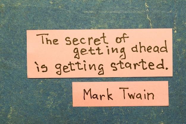 앞서가는 비결은 시작하는 것입니다 - 유명한 미국 작가 마크 트웨인이 빈티지 판지 판지에 분홍색 메모로 해석을 인용합니다.