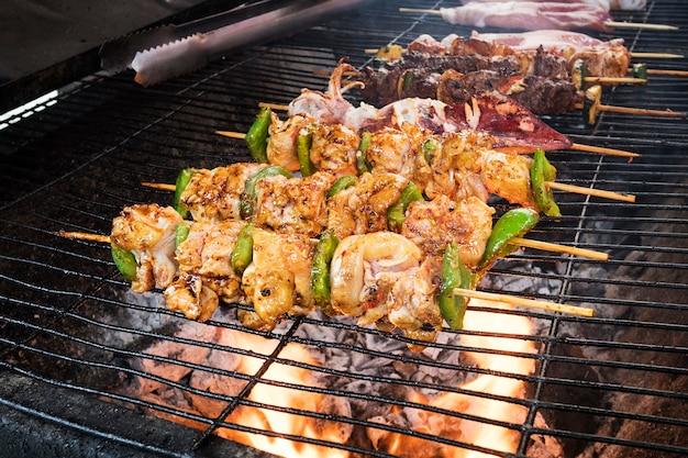 竹の棒にセレクティブフォーカスポークバーベキュー串。バーベキュー、タイ、ベトナム料理、中華料理のストーブで野菜を使ったグリル料理。野外でのバーベキュー。