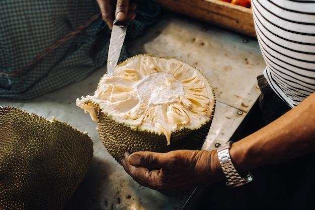 売り手は観光客のためにジューシーで熟したジャックフルーツをカットします。モーリシャスのポートルイスの都市市場。