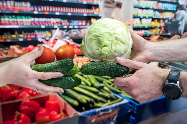 売り手は店で買い手に野菜を与えます。ショッピングと健康的なライフスタイルの概念