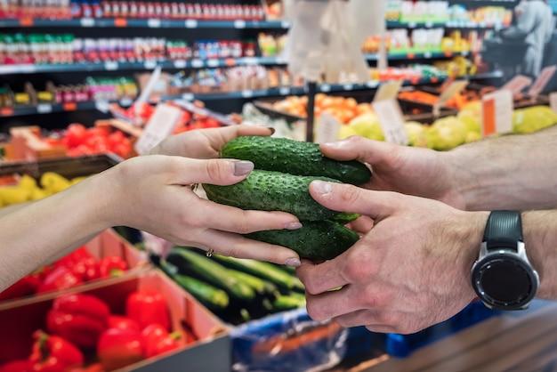 売り手は店で買い手に野菜を与えます