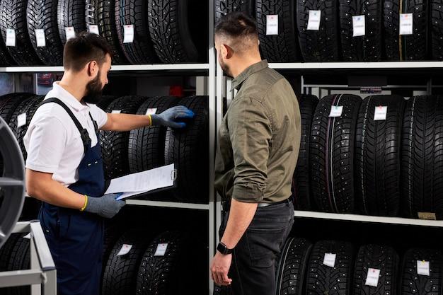 판매자는 새로운 고무 바퀴, 타이어, 자동차 림을 제공합니다. 남성 고객이 자동차 정비소에서 구매하러 왔습니다. 다양 한 타이어를 보여주는 자동차 정비사