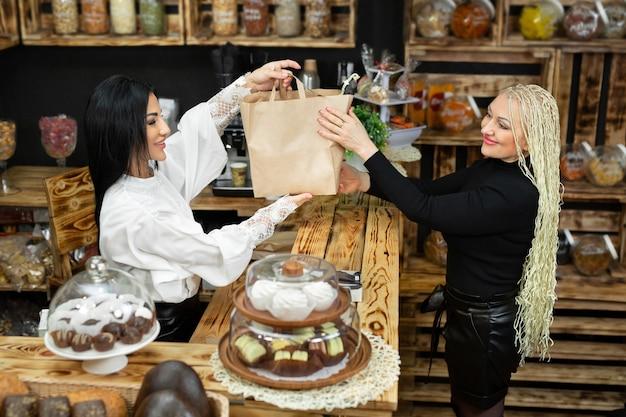 売り手は、食料品店の女性顧客に製品が入った紙袋を渡します。