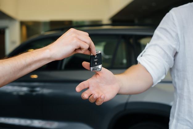 売り手は若い家族に新しい車の鍵を渡します