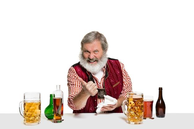 흰색 벽에 격리에서 맥주와 함께 수석 전문가 남성 바텐더. 국제 바텐더의 날, 바, 술, 레스토랑, 맥주, 파티, 펍, 성 패트릭의 날 축하 개념