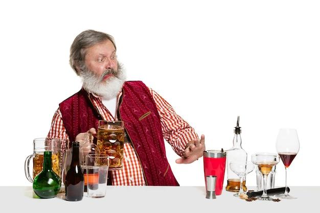 白い背景で隔離のスタジオでビールを飲みながら上級専門家の男性バーテンダー。国際的なバーテンダーの日、バー、アルコール、レストラン、ビール、パーティー、パブ、聖パトリックの日のお祝いのコンセプト