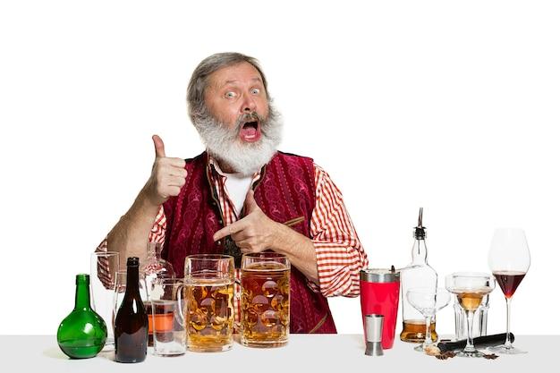 흰 벽에 고립 된 맥주와 함께 수석 전문가 남성 바텐더. 국제 바텐더의 날, 바, 술, 레스토랑, 맥주, 파티, 펍, 성 패트릭의 날 축하 개념