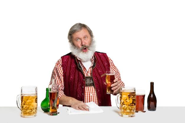 白い壁に分離されたビールを持つ上級専門家の男性バーマン。国際バーテンダーの日、バー、アルコール、レストラン、ビール、パーティー、パブ、聖パトリックの日のお祝いのコンセプト