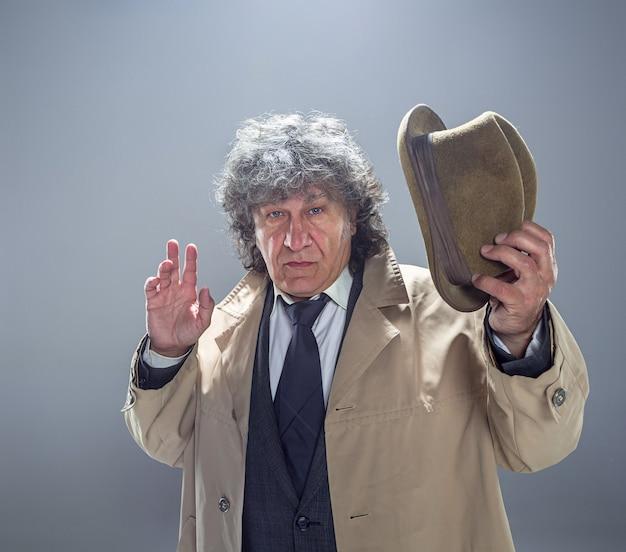 灰色のスタジオの背景に探偵またはマフィアのボスとして年配の男性