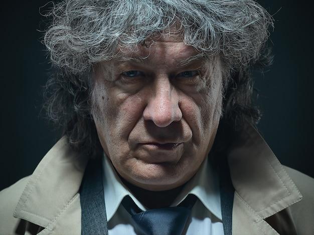 Старший мужчина как детектив или босс мафии на серой студии