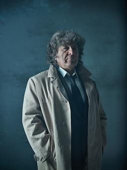 灰色のスタジオのマフィアの探偵またはボスとしての年配の男性