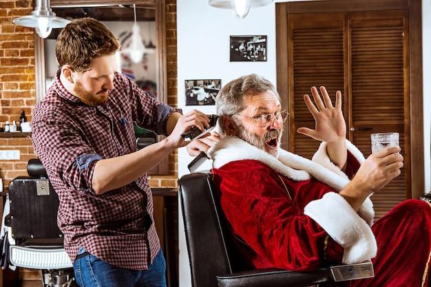 Пожилой мужчина в костюме санта-клауса бреет своего личного хозяина в парикмахерской перед рождеством