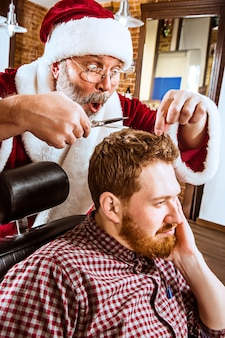 Старший мужчина в костюме санта-клауса работает личным мастером с ножницами в парикмахерской перед рождеством