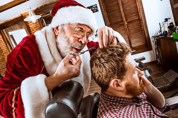 크리스마스 전에 이발소에서 가위로 개인 마스터로 일하는 산타 클로스 의상 수석 남자