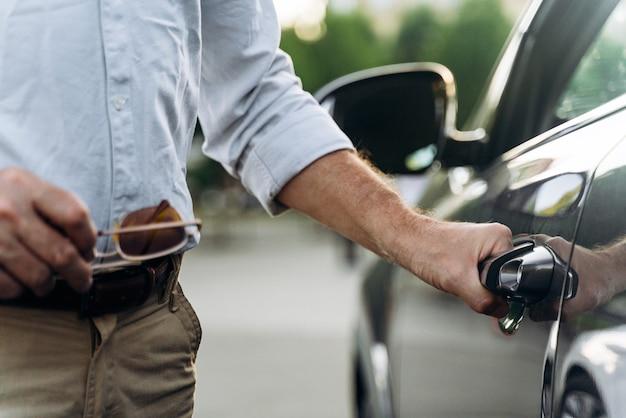 수석 남자는 열쇠가 없는 액세스로 자신의 차 문을 엽니다. 문 손잡이에 손을 닫습니다.