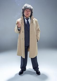 探偵または灰色のスタジオの背景にマフィアのボスとして葉巻と年配の男性
