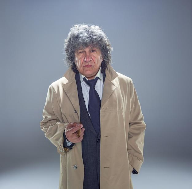 Старший мужчина с сигарой как детектив или босс мафии на сером пространстве студии