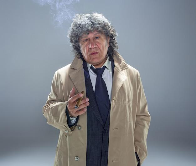 灰色のスタジオスペースで探偵またはマフィアのボスとして葉巻を持つシニア男性